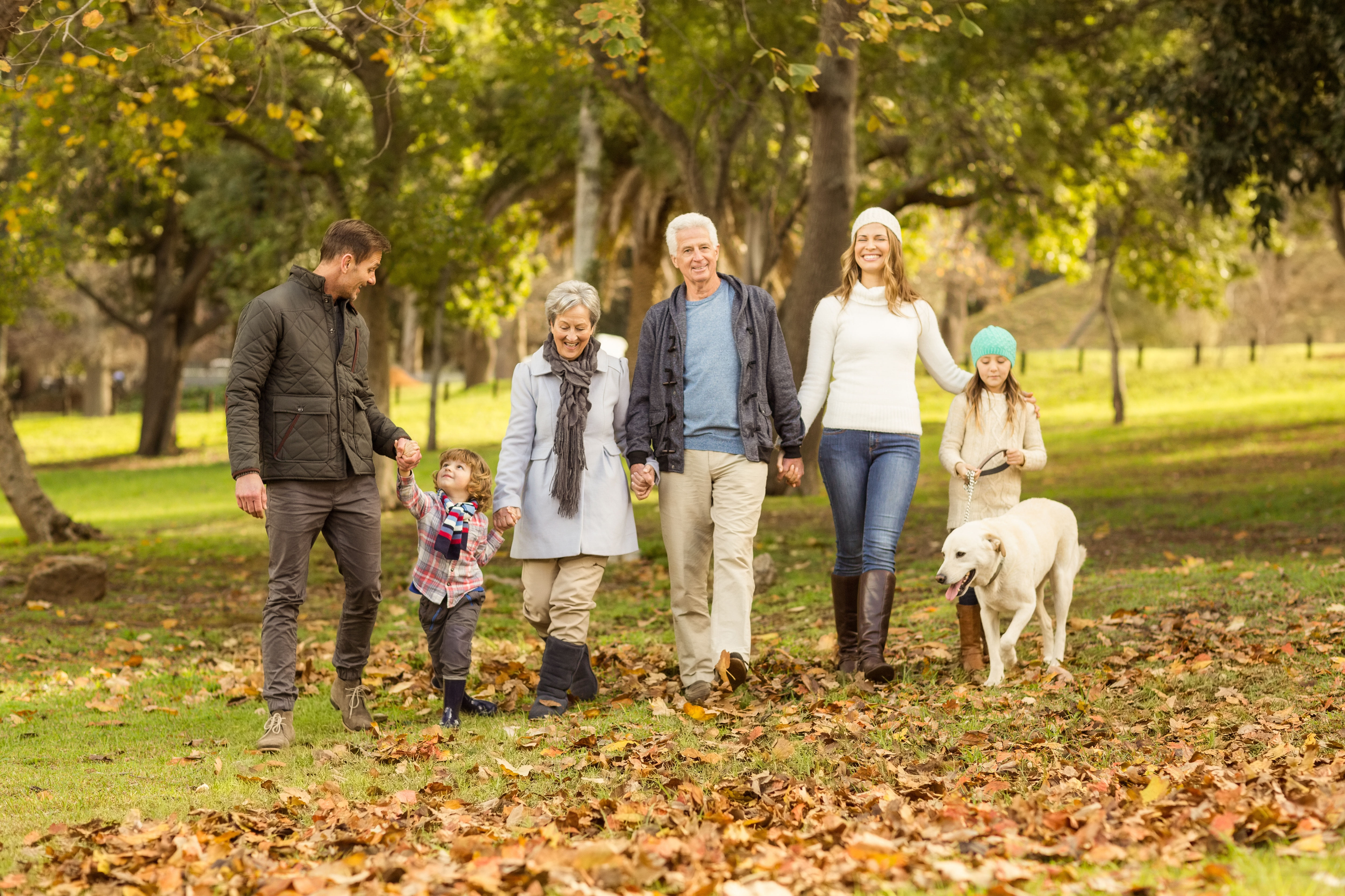 Smiling extended family walking together on an autumns day